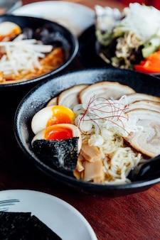 Japanische nudel in misosuppe mit chashu-schweinefleisch, gekochtem ei, trockenem algen