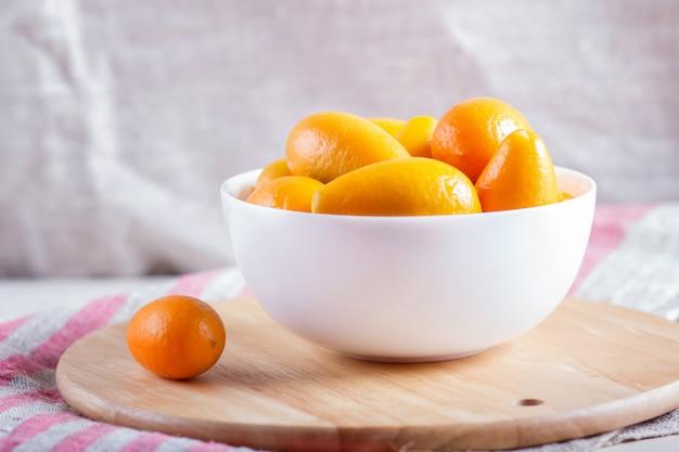 Japanische orangen in einer weißen platte auf einem hölzernen küchenbrett