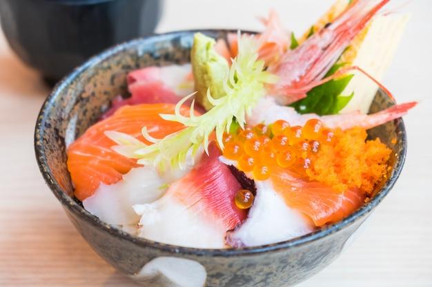 Japanische reisschale mit sashimi-meeresfrüchten an der spitze