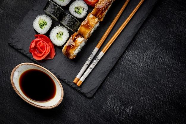 Japanische rollen auf schwarzem schieferbrett und draufsicht des schwarzen hintergrunds