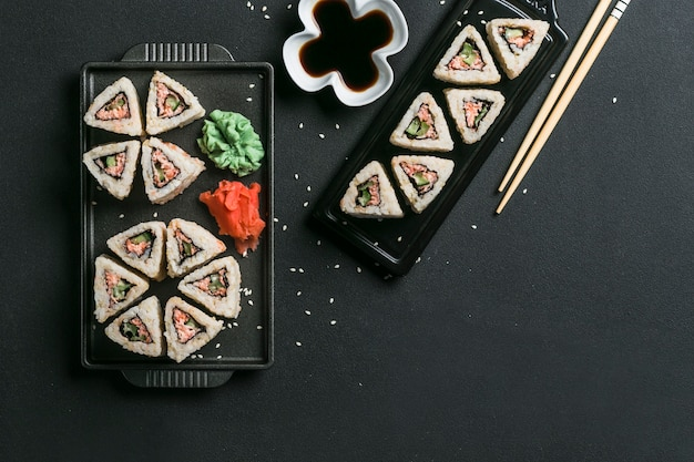 Japanische surimi-quinoa-brötchen mit eingelegtem ingwer und wasabi-sauce auf einem schwarzen teller mit stäbchen auf dunklem hintergrund.