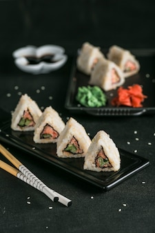 Japanische surimi-quinoa-brötchen mit eingelegtem ingwer und wasabi-sauce auf einem schwarzen teller mit stäbchen