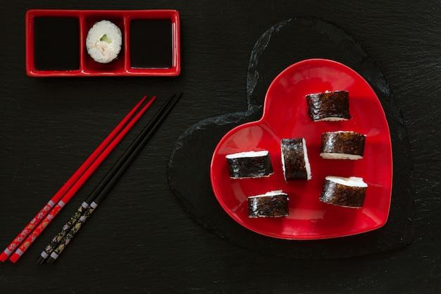Japanische sushi mit sojasoße auf rotem teller der herzform mit essstäbchen.