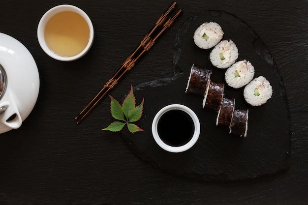 Japanische sushi mit sojasoße auf schwarzem teller der herzform mit essstäbchen und traditionellem tee.