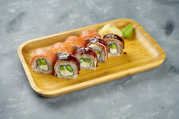 Japanische sushi-rolle - philadelphia mit lachs und aal, frischkäse und avocado auf einem holzteller auf einem grauen tisch. japanische küche. nahansicht