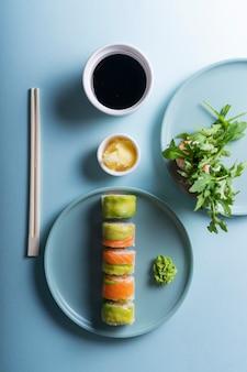 Japanische sushi-rollen mit avocado und lachs im modernen minimalistischen stil. auf einem blauen hintergrund mit harten schatten