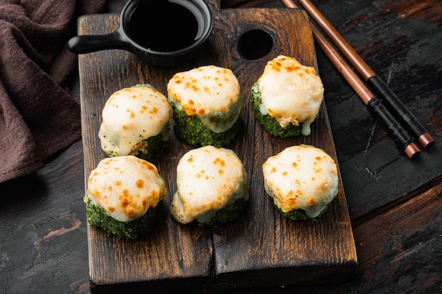 Japanische sushi-rollen namens baked ebi mit wasabi- und lachsfisch-set, auf altem dunklem holztischhintergrund