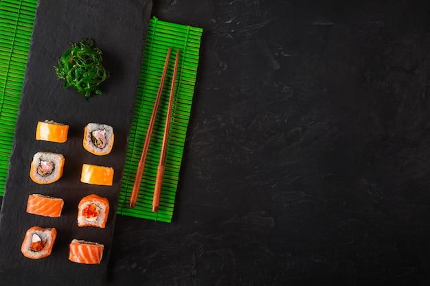 Japanische sushiessstäbchen über sojasoßenschüssel, reis auf schwarzem steinhintergrund. draufsicht mit textfreiraum