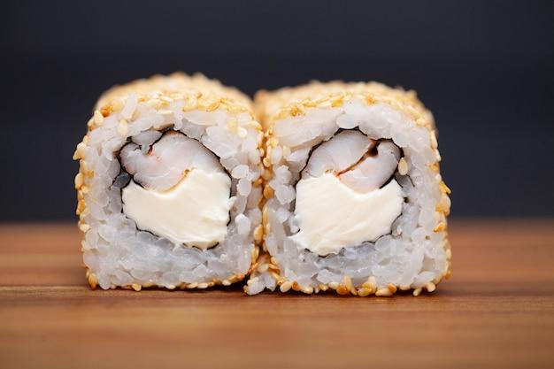 Japanische sushirolle mit lachsen und gurke auf dunkelheit