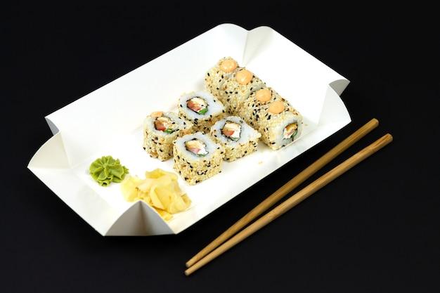 Japanische sushirollen in der einwegbox des weißen öko-papiers auf dunklem hintergrund