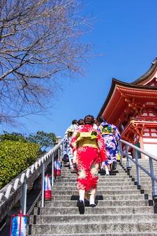 Japanische touristen und ausländer ziehen sich ein yukata-kleid an, um das innere des kiyomizu-dera-tempels zu besuchen
