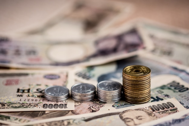 Japanische yen-banknoten und japanische yen prägen schichten auf boden.