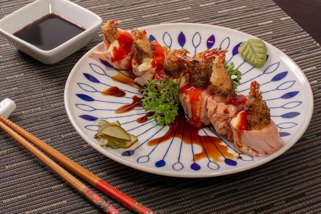 Japanischer, asiatischer lebensmittelteller mit garnele und salmon sushi mit veggies und soße