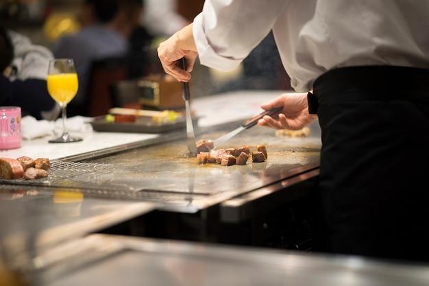 Japanischer chef, der wagyu-rindfleisch teppanyaki art kocht