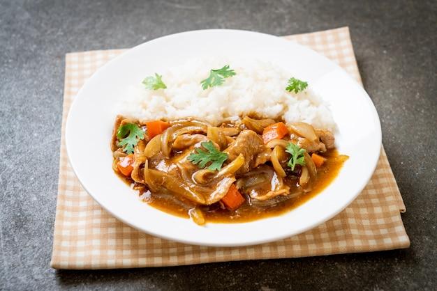 Japanischer curryreis mit geschnittenem schweinefleisch, karotte und zwiebeln
