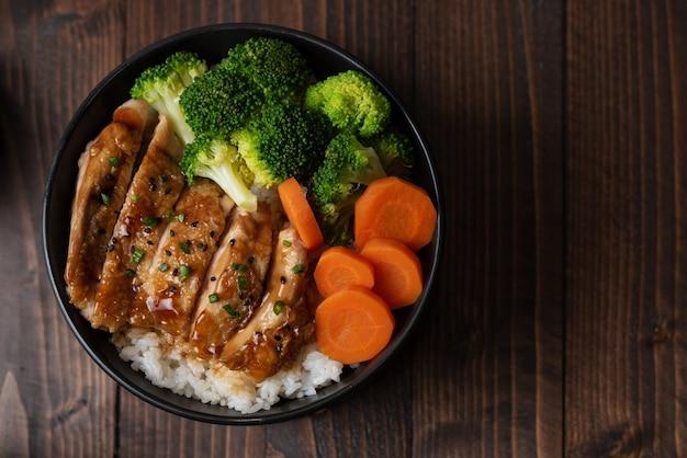Japanischer essensstil: draufsicht auf hausgemachtes hühnchen-teriyaki, gegrillt mit reis, karotten, brokkoli, auf die schwarze schüssel legen und auf den holztisch legen
