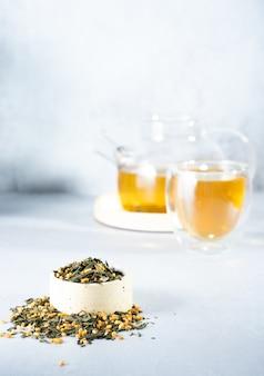 Japanischer grüner tee genmaicha.teeblätter mit gebratenem braunem reis auf einem hellgrauen hintergrund mit einem schatten. schlankheitstrend-teekonzept. eine tasse tee. eine durchsichtige teekanne brauen
