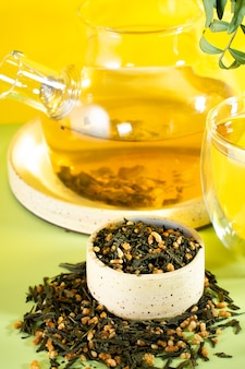Japanischer grüner tee genmaicha.teeblätter mit gebratenem braunem reis auf einem leuchtend gelben hintergrund mit einem schatten. schlankheits-trend-tee-konzept. eine tasse tee. eine durchsichtige teekanne brauen