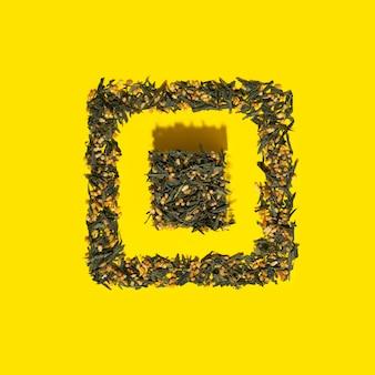 Japanischer grüntee genmaicha. teeblätter mit gebratenem braunem reis in würfelform auf hellgelbem hintergrund mit schatten. schlankheits-trend-tee-konzept. natürliches produkt. selbstfürsorge und gesundheit