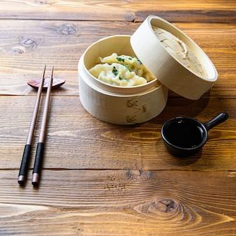 Japanischer gyoza oder knödelsnack mit sojasauce im holzdampfer