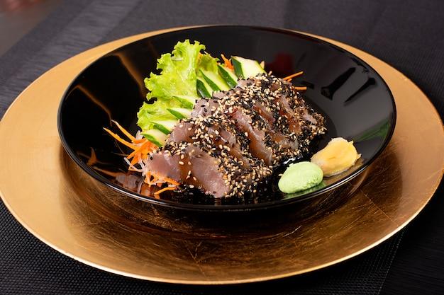 Japanischer lebensmittelteller mit gebratenem thunfisch und gemüse auf einem schwarzen schönen teller, köstliches asiatisches lebensmittel