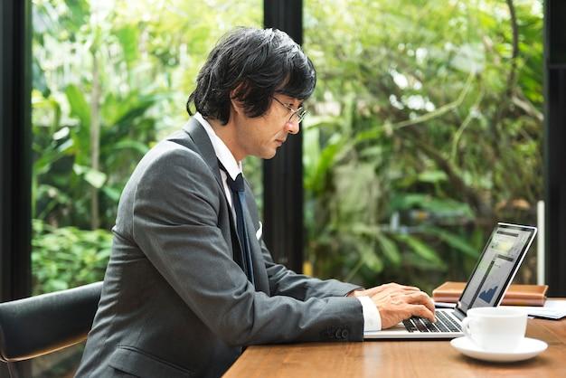 Japanischer mann, der an einem laptop arbeitet