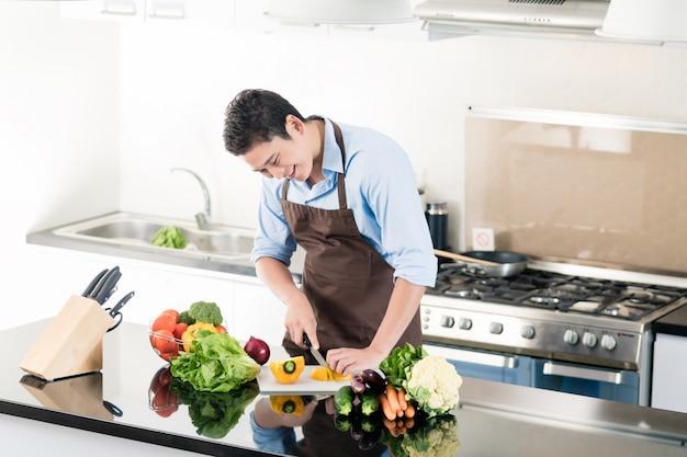 Japanischer mann, der salat zubereitet und in der küche kocht
