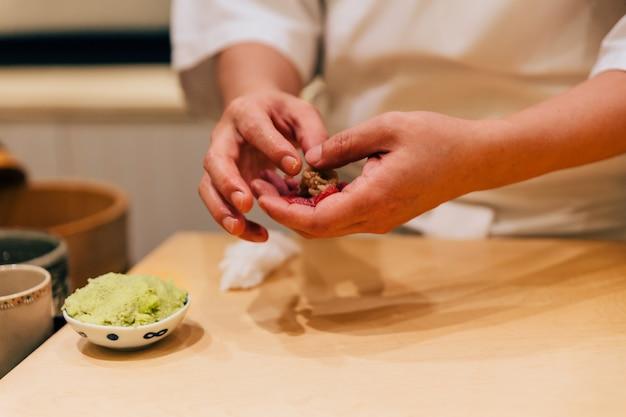 Japanischer omakase-chef, der chutoro-sushi (mittelfetter roter thunfisch) macht.