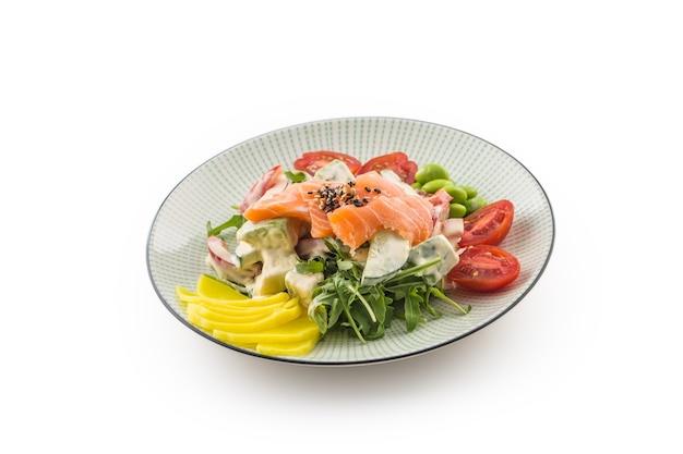Japanischer salat mit fisch, lachs und gemüse und stäbchen auf weißem hintergrund.