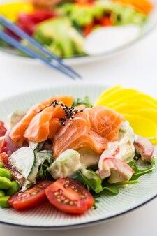 Japanischer salat mit fischlachs und gemüse und stäbchen.
