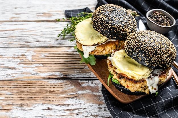 Japanischer schwarzer burger mit rührei und rucola. cheeseburger mit schwarzem brötchen.