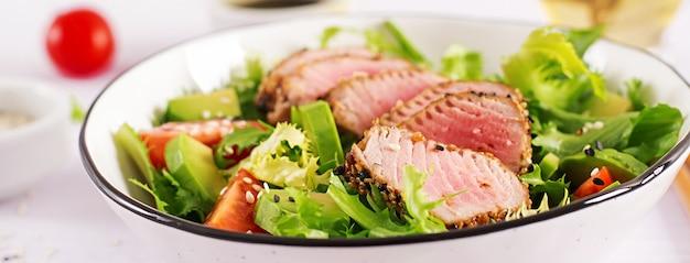 Japanischer traditioneller salat mit stücken von mittel-seltenem gegrilltem ahi-thunfisch und sesam mit frischem gemüse auf einer schüssel.