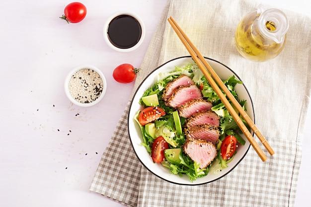 Japanischer traditioneller salat mit stücken von mittel-seltenem gegrilltem ahi thunfisch und sesam mit frischem gemüse auf einer schüssel.