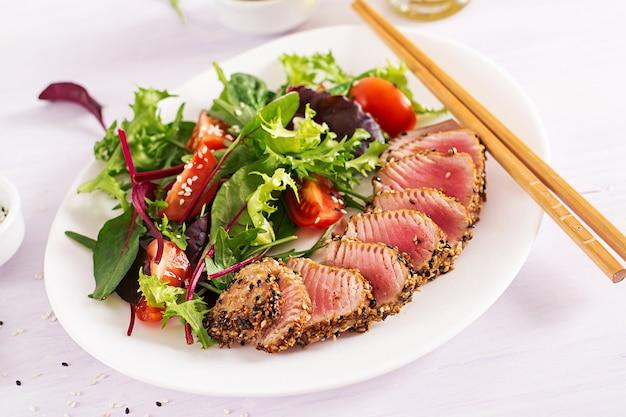 Japanischer traditioneller salat mit stücken von mittel-seltenem gegrilltem ahi-thunfisch und sesam mit frischem gemüsesalat auf einem teller.