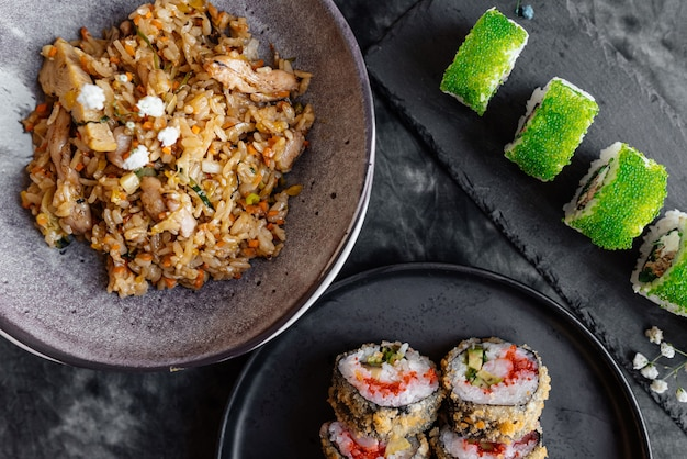 Japanisches abendessen mit sushi und reis auf einem tisch mit schwarzer oberfläche