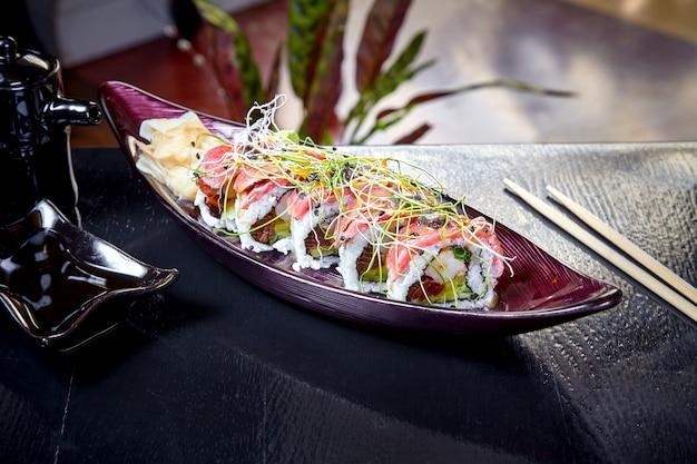 Japanisches brötchensushi der modernen küche mit garnelen und roastbeef. nahaufnahme auf sushi mit avocado und lachs. gesunde meeresfrüchte. fisch. diät, ausgewogenes essen. speicherplatz kopieren. japanische küche