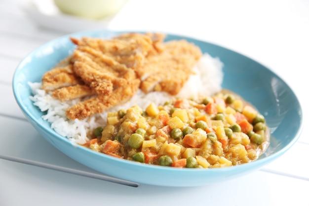 Japanisches essen curryreis mit gebratenem schweinefleisch auf holzhintergrund