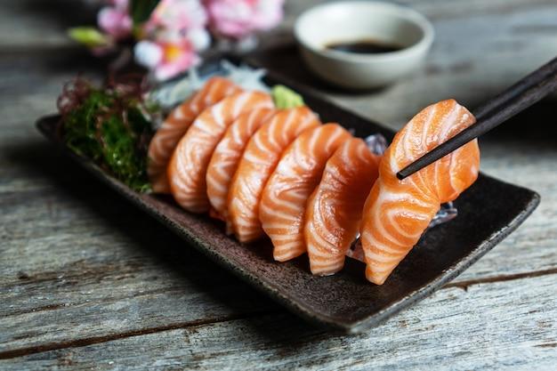 Japanisches essen des lachssashimi mit sojasauce auf holztisch