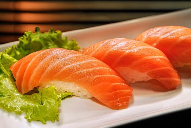 Japanisches essen drei lachs-niguiri mit reis in einem weißen quadratischen teller