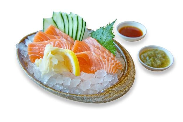 Japanisches essen, frischer lachs in einer schüssel auf eis mit meeresfrüchtesauce und gurkenscheiben, fokus selektiv.
