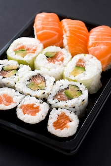 Japanisches essen: maki und nigiri sushi legen schwarzen hintergrund