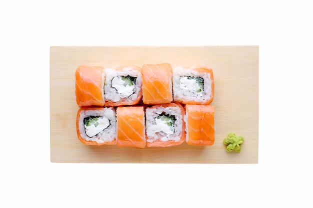 Japanisches essen restaurant lieferung, sushi-set. sushi rollt kalifornien mit lachs und käse an der hölzernen platte lokalisiert. draufsicht