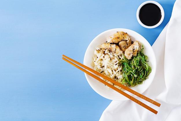 Japanisches essen. schüssel reis, gekochter weißer fisch und wakame chuka oder algensalat.