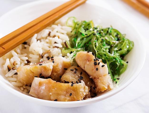Japanisches essen. schüssel reis, gekochter weißfisch und wakame chuka oder algensalat.