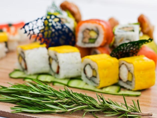 Japanisches essen - sushi, sashimi, brötchen auf einem holzbrett. isoliert