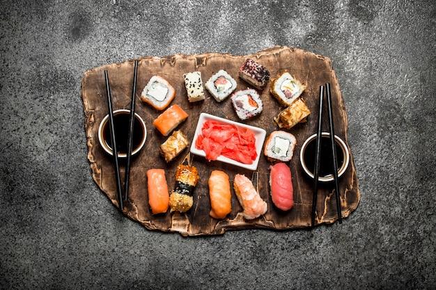 Japanisches essen. sushi und brötchen frische meeresfrüchte mit sojasauce und eingelegtem ingwer. auf rustikalem hintergrund.