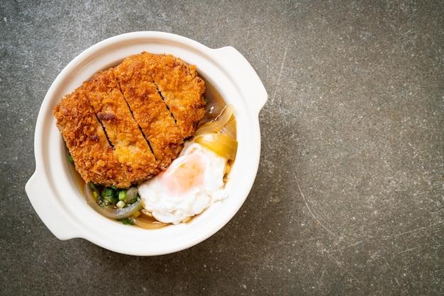 Japanisches gebratenes schweinekotelett (katsudon) mit zwiebelsuppe und ei - asiatische art zu essen