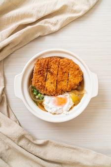 Japanisches gebratenes schweinekotelett mit zwiebelsuppe und ei