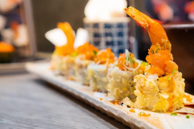 Japanisches gericht, crunchy shrimp tempura roll, serviert auf einem rechteckigen teller auf einem holztisch