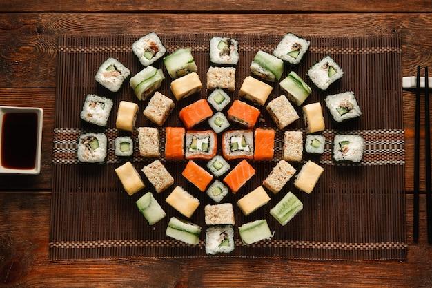 Japanisches köstliches und frisches set bunter sushi-rollen, serviert auf brauner strohmatte, flach. lebensmittelkunst, schöne verzierung, menüfoto des luxusrestaurants.